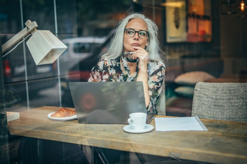 old businesswoman sitting in a cafe alone thinking deeply